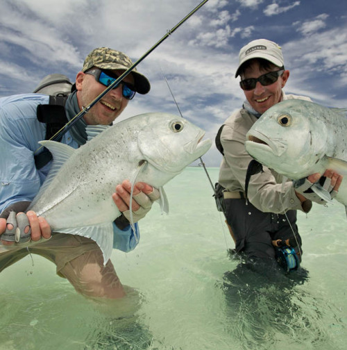 Two guys showing off their GT's caught with Alphonse Fishing Co™