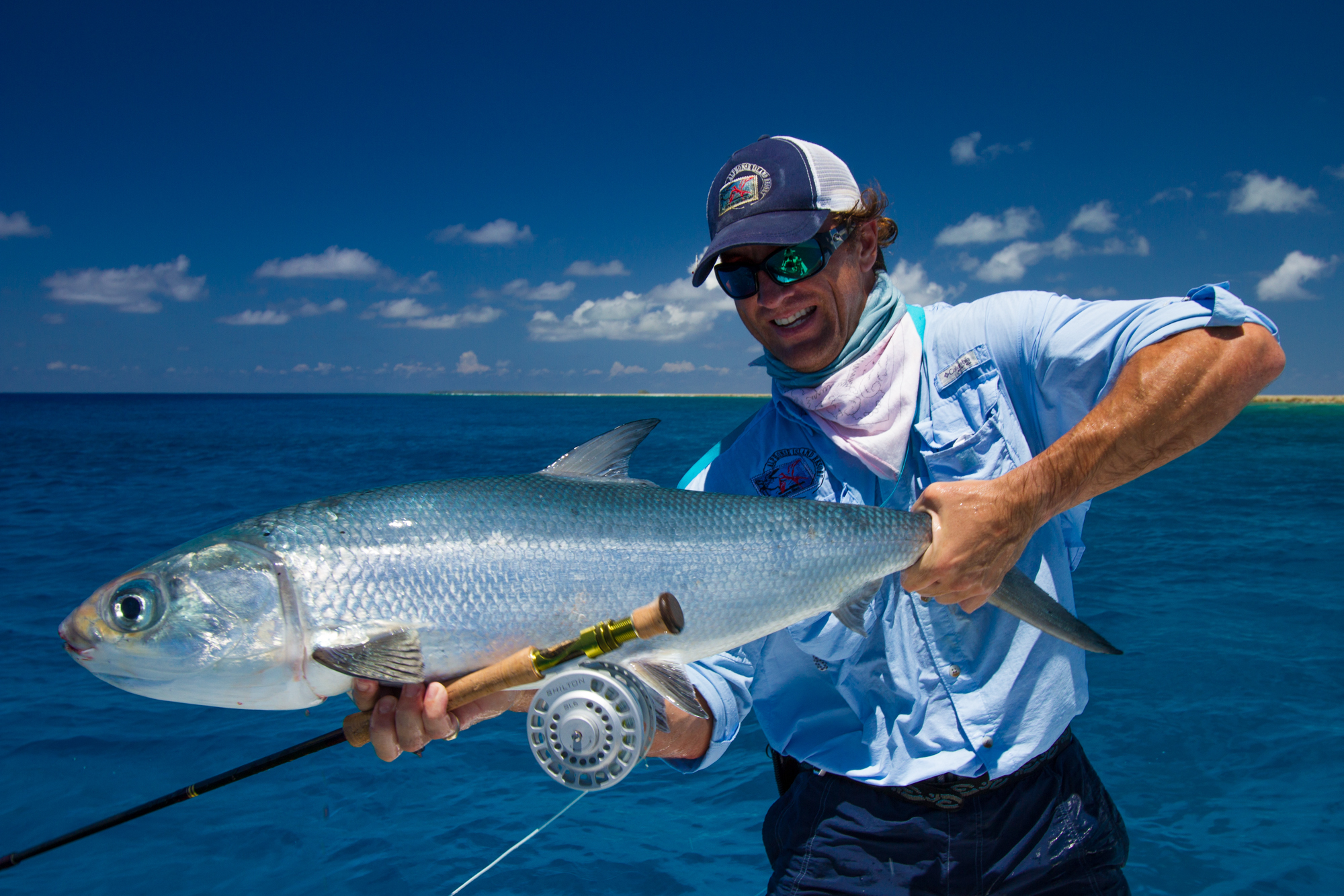 Happy fly fisherman proudly holding the milkfish caught on a fly.