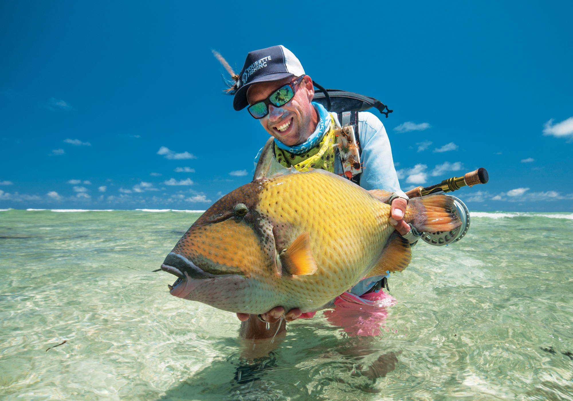 Happy fly fisherman holding a moustache triggerfish caught on a fly at Astove Atoll.