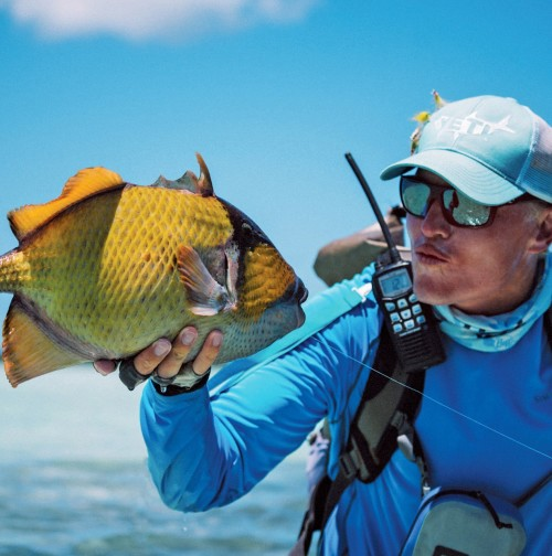 Fly fisherman blowing a kiss to his moustache triggerfish caught on a fly at Cosmoledo Atoll.