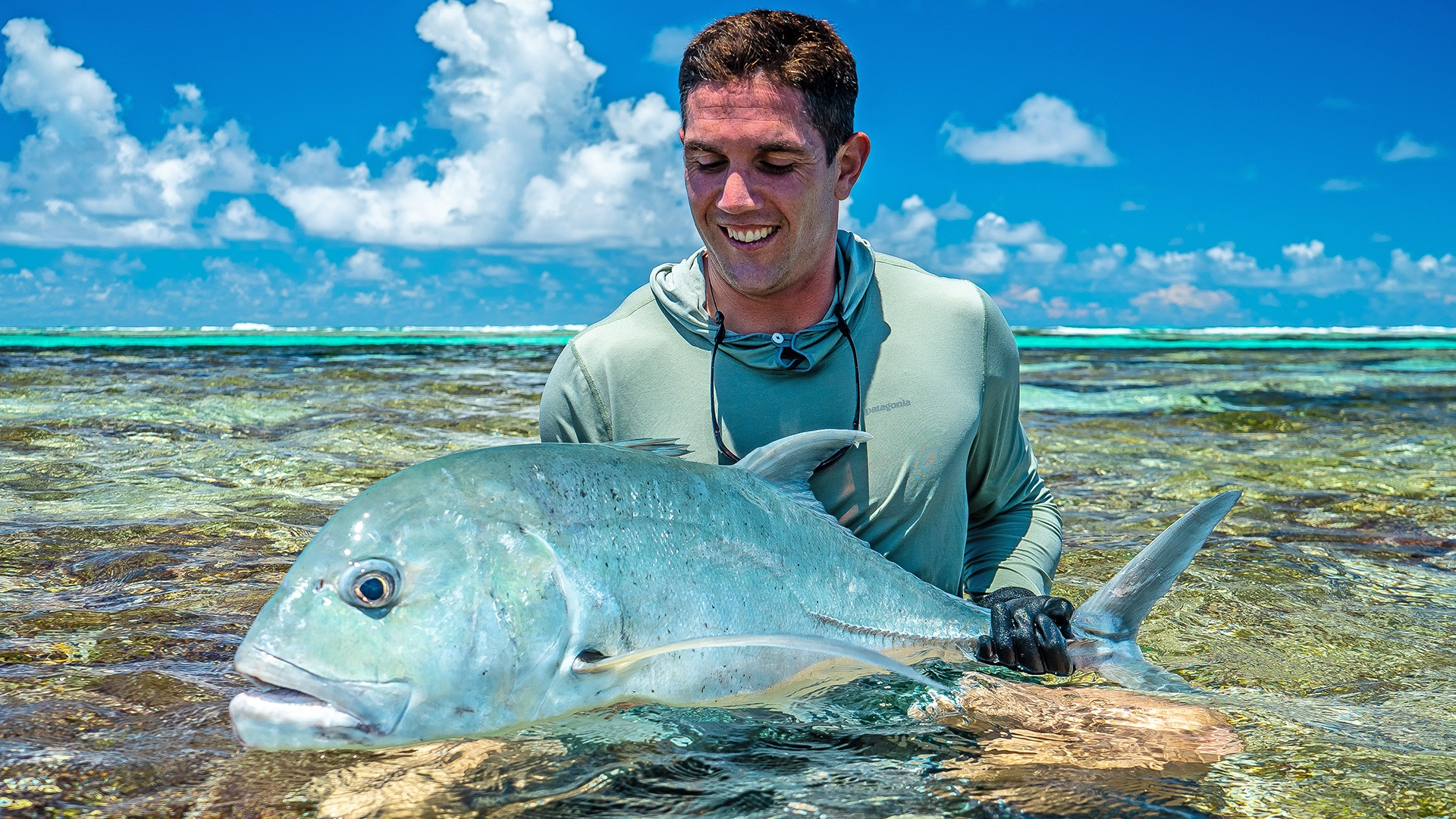 Happy fly fisherman with his bluefine trevally caught on a fly at Farquhar Atoll with Alphonse Fishing Co™